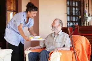 Caregiver handing out the meal to an elderly man.